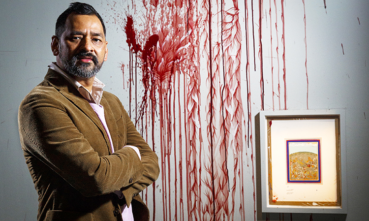 Imran Qureshi stands next to his artwork (courtesy The Barbican Centre) - Where the Shadows are so Deep by Imran Qureshi