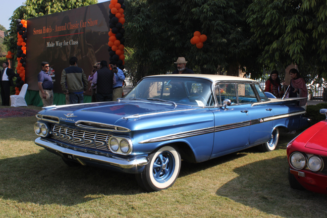 A classic blue Chevrolet Impala from the '60s