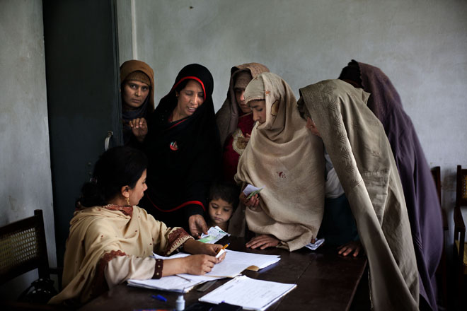 Women gather around a polling officer to cast their vote during the General Elections in Islamabad, Pakistan on May 11, 2013