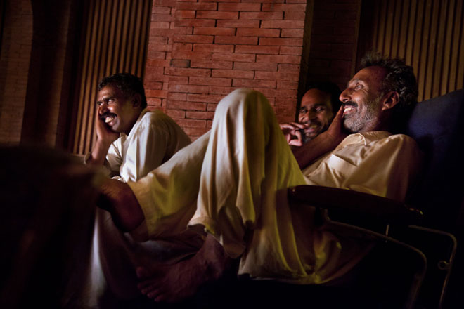 Male audience members make themselves comfortable at a theatre in Islamabad during a drama performance