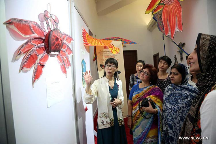Visitors look at a Chinese kite during the exhibition - Chinese Kite Exhibition in Islamabad