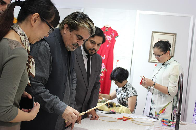 DG PNCA, Mr. Jamal Shah examines embroidered Chinese fans at the exhibition of Chinese Silk, Porcelain and Tea at PNCA