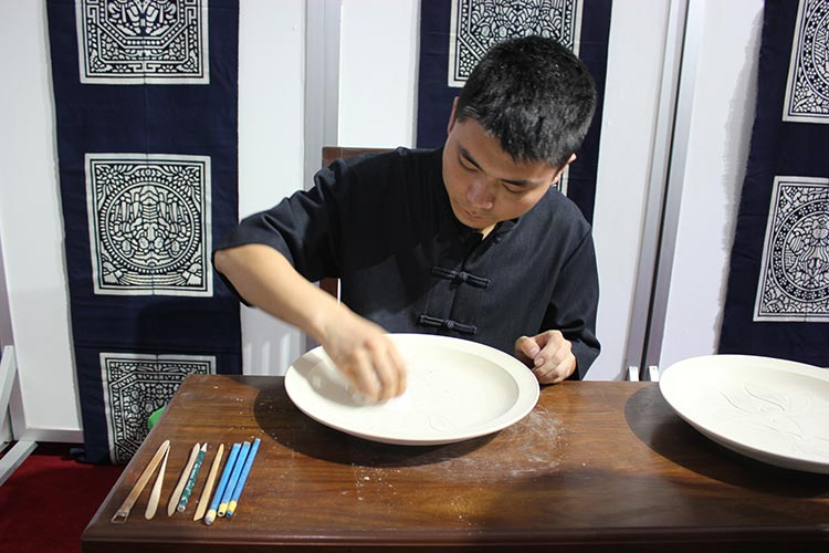 Mr. Jin Xin carving a pattern on porcelain