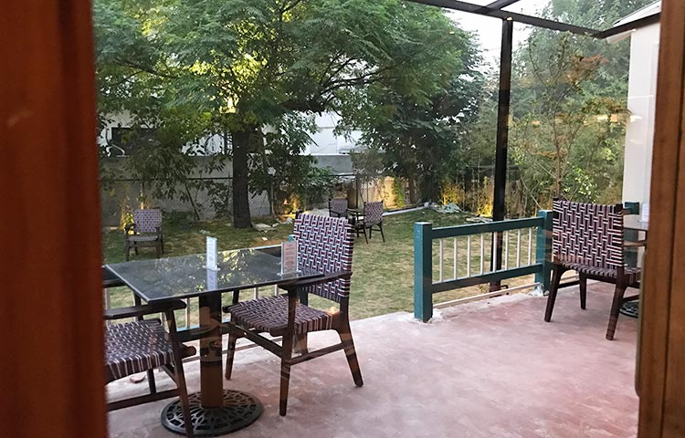 The outdoor seating area and garden - Food Review of English Tea House, Islamabad