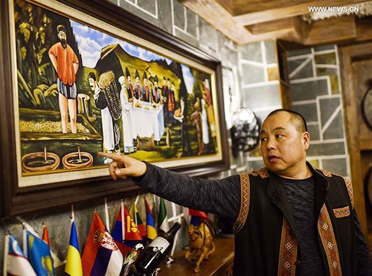 Tong Jiansheng, a merchant, introduces a Georgian style painting at his restaurant in Urumqi