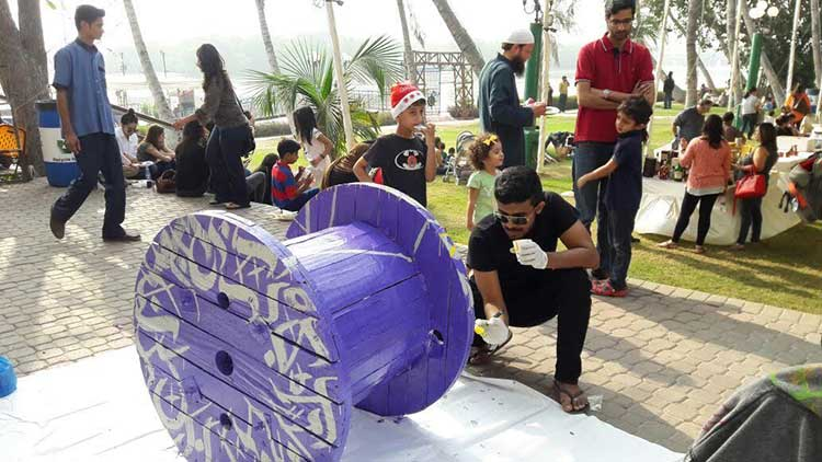 Graffiti and performing artist Sanki King paints his reel as visitors watch - Karachi Biennale: Reel On Hai
