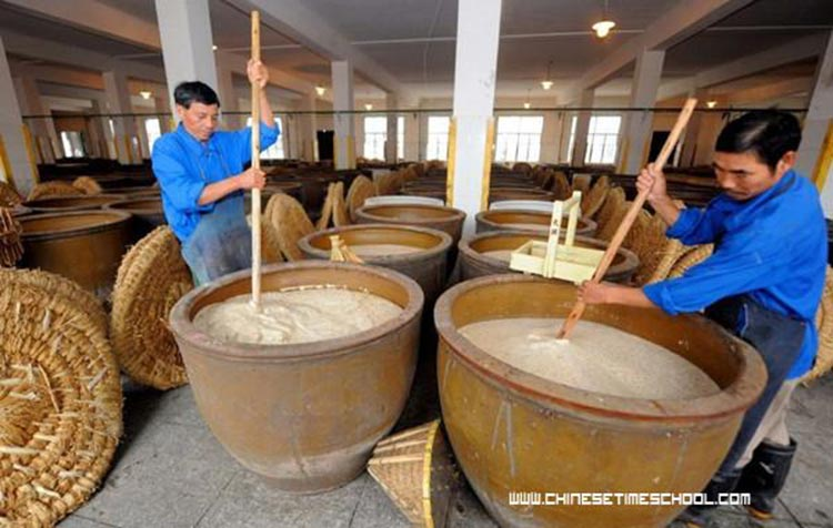 Organic Food of China - Workers churn up parboiled rice for brewing Shaoxing rice wine
