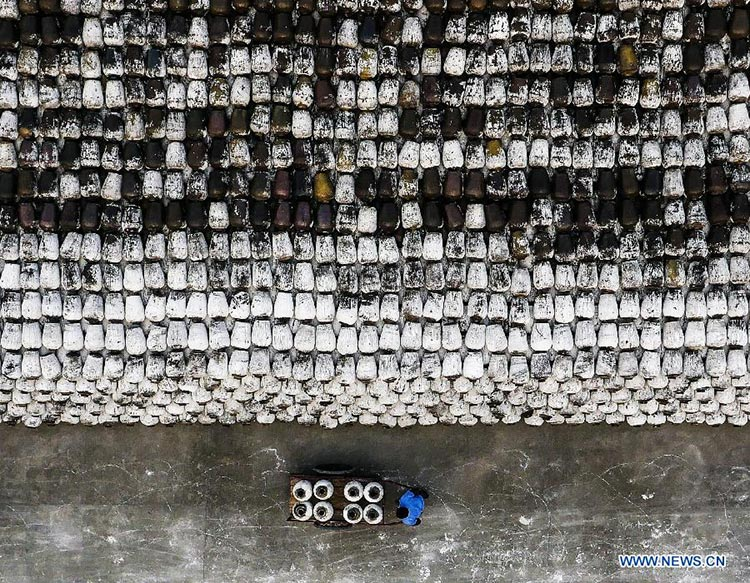 Organic Food of China - A worker, surrounded by piles of jars, carries some more for brewing Shaoxing rice wine